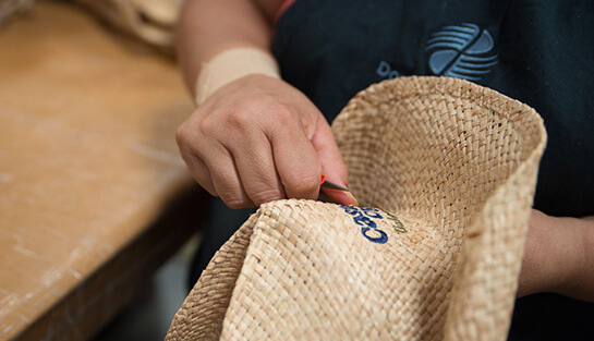 A woman cleaning up embroidery on a straw hat