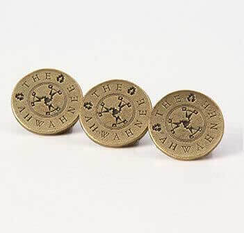 Three circular gold pins with text and a logo
