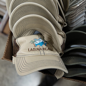 Embroidered caps stacked in a box
