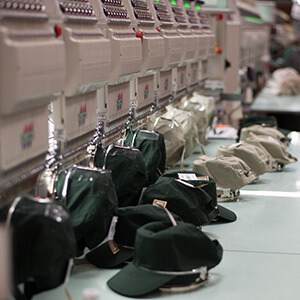 Production line of embroidery machines with hats resting on the counter