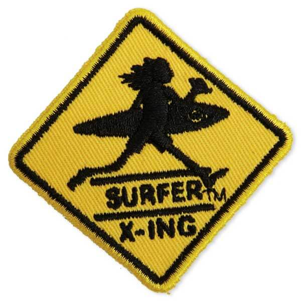 Surfer crossing sign patch in yellow and black with a man and his surf board walking