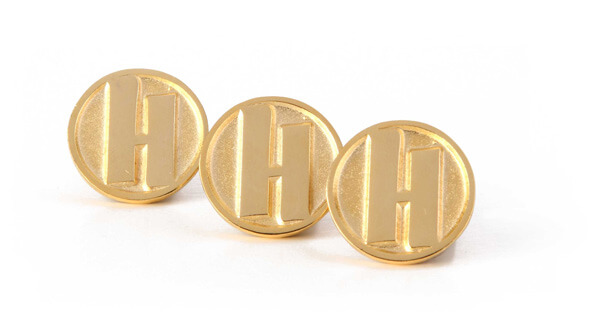 Gold circular pins with a branded logo with the letter H