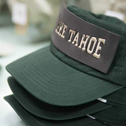 Stacked green hats with Lake Tahoe being added to the front